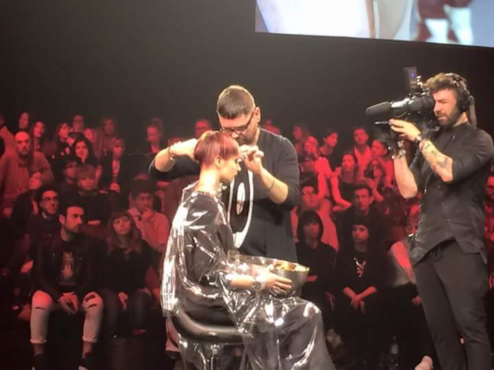 Man styling woman's hair on stage