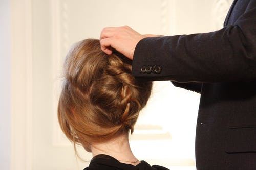 Woman having hair styled into an updo